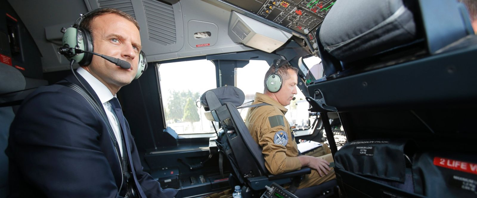 French President Emmanuel Macron is seated in the cockpit of an Airbus A400M turboprop transport plane before taking off from Villacoublay military airbase near Paris.